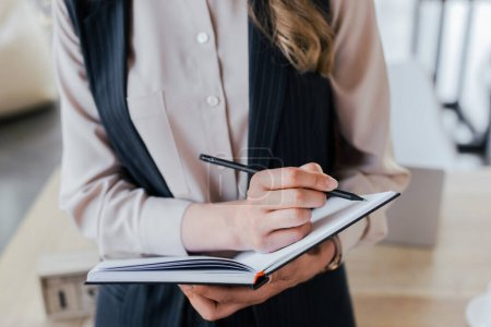 Photo for Cropped view of businesswoman writing in notebook while standing in office - Royalty Free Image