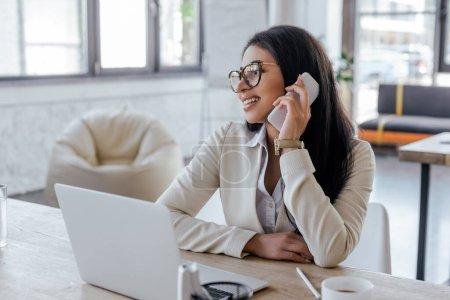 Photo pour Foyer sélectif de femme d'affaires heureuse dans les lunettes parler sur smartphone près d'un ordinateur portable - image libre de droit