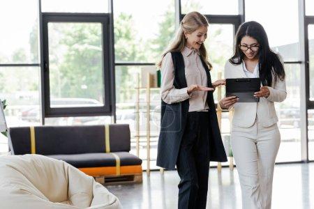 foyer sélectif des femmes d'affaires excitées regardant le presse-papiers