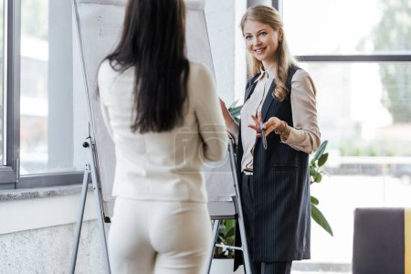 Photo for Selective focus of happy businesswoman holding marker pen near flipchart and looking at coworker - Royalty Free Image
