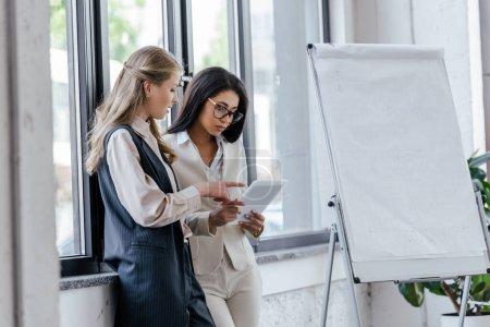 Photo pour Foyer sélectif de femme d'affaires pointant du doigt la tablette numérique près de collègue attrayant dans les lunettes - image libre de droit