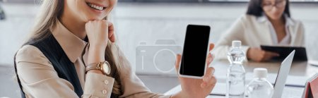 panoramic crop of businesswoman holding smartphone with blank screen