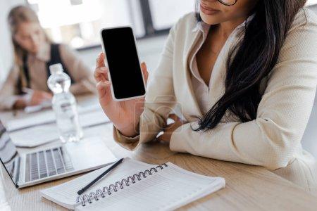 Photo pour Vue recadrée de femme d'affaires tenant smartphone avec écran vierge - image libre de droit