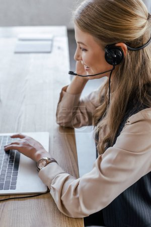 Photo for Side view of cheerful operator in headset smiling near laptop - Royalty Free Image