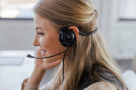 Photo for Side view of cheerful operator in headset smiling in office - Royalty Free Image