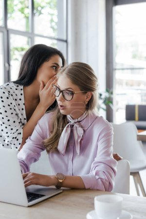 Photo for Businesswoman whispering in ear of surprised coworker in glasses while gossiping in office - Royalty Free Image