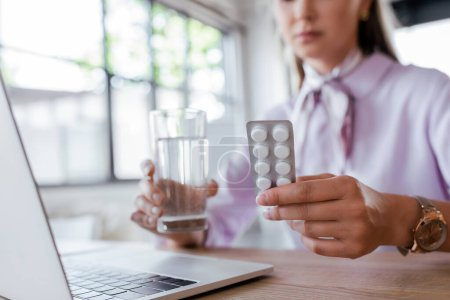 Photo for Cropped view of woman holding glass of water and blister pack with pills near laptop - Royalty Free Image
