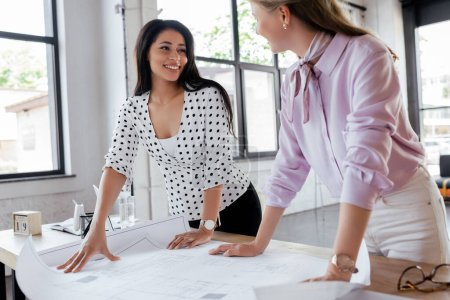 Photo for Selective focus of happy businesswomen looking at each other near blueprints in office - Royalty Free Image