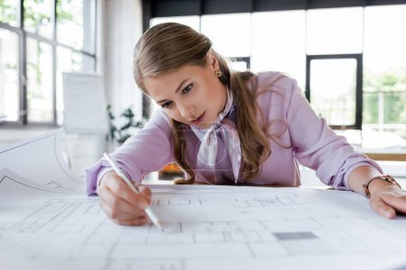 Photo pour Foyer sélectif de femme d'affaires attrayante dessin des plans dans le bureau - image libre de droit
