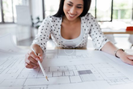 Photo for Selective focus of happy businesswoman drawing blueprints in office - Royalty Free Image