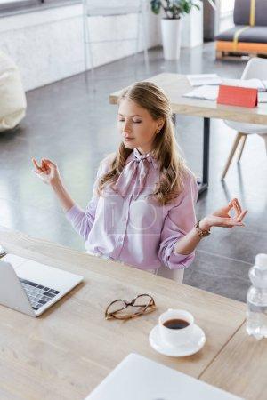Photo pour Femme d'affaires avec les yeux fermés méditant près de la table avec ordinateur portable et tasse au bureau - image libre de droit