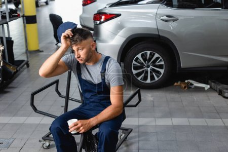 Photo for Tired mechanic holding cap and paper cup while sitting near cars in garage - Royalty Free Image