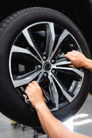 cropped view of technician touching wheel disk while fixing car