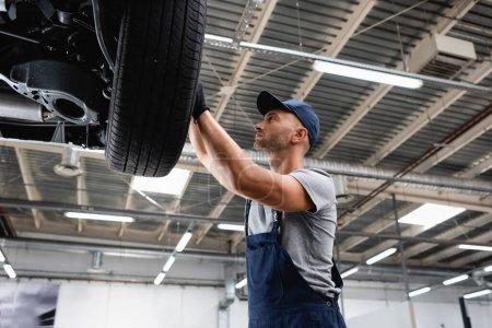 Photo pour Vue à faible angle du technicien touchant pneu de voiture dans la station-service - image libre de droit