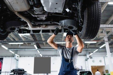 Photo pour Vue à angle bas du technicien en casquette et salopette réparation de voiture dans la station-service - image libre de droit