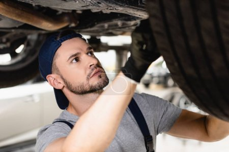 selective focus of mechanic in rubber glove and cap fixing car