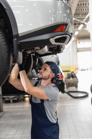 Photo pour Foyer sélectif de beau mécanicien en uniforme et fixation de capuchon voiture - image libre de droit