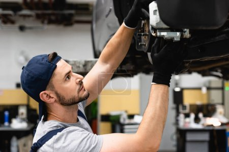 Photo for Side view of mechanic in cap and rubber gloves fixing vehicle - Royalty Free Image