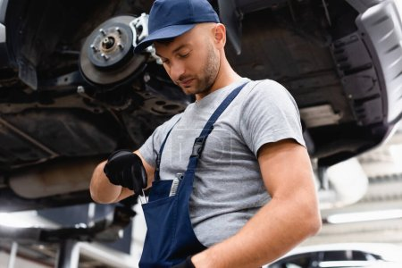 Photo for Low angle view of mechanic in overalls taking wrench from pocket near car - Royalty Free Image