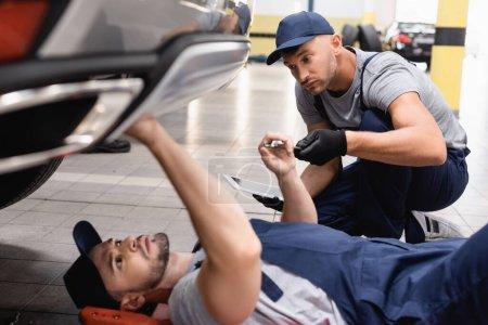 Photo pour Foyer sélectif du mécanicien en uniforme tenant tablette numérique et regardant collègue couché et réparer l'automobile dans le service de voiture - image libre de droit