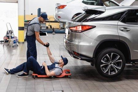 Photo pour Mécanicien tenant la main avec un collègue dans le chapeau couché près des voitures - image libre de droit