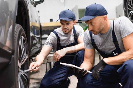 Foto de Enfoque selectivo de mecánico celebración tableta digital cerca de compañero de trabajo con llave reparación de automóviles - Imagen libre de derechos