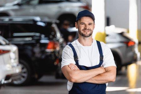 Photo pour Heureux mécanicien en uniforme et casquette debout avec les bras croisés en service de voiture - image libre de droit