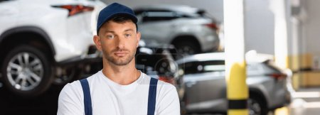 Photo for Panoramic crop of technician in cap looking at camera in car service - Royalty Free Image