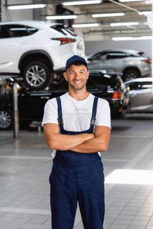 Photo pour Heureux mécanicien en uniforme et casquette debout avec bras croisés dans la station-service - image libre de droit
