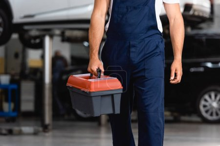Photo pour Vue recadrée du mécanicien dans la boîte à outils de maintien uniforme dans la station-service - image libre de droit