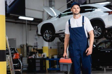 gutaussehender Mechaniker in Overalls und Mütze mit Werkzeugkiste im Autoservice
