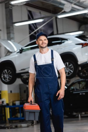 Photo for Happy mechanic in overalls and cap holding toolbox in car service - Royalty Free Image