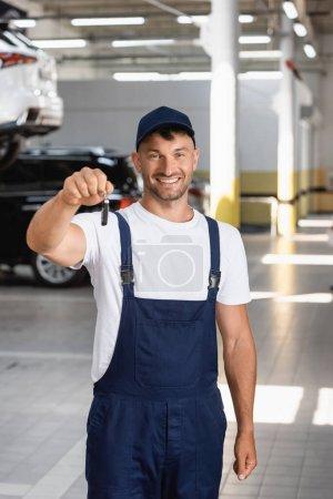 Photo pour Heureux mécanicien en uniforme et capuchon tenant clé de voiture - image libre de droit