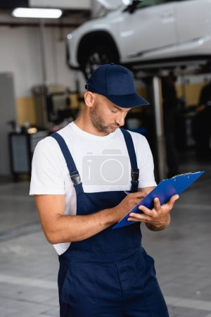 Photo for Handsome mechanic in uniform and cap writing while holding clipboard - Royalty Free Image
