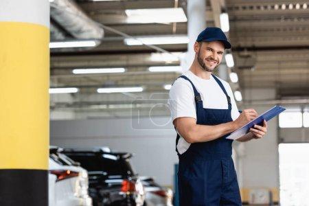 Photo pour Heureux mécanicien en uniforme et Cap écriture tout en tenant presse-papiers et stylo près des voitures - image libre de droit