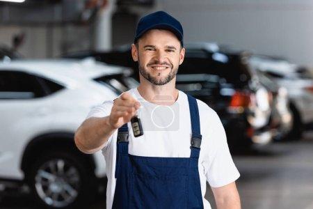 Photo pour Mécanicien joyeux en uniforme et capuchon tenant clé de voiture - image libre de droit