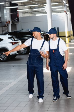 Photo for Happy mechanic in uniform holding digital tablet and pointing with finger at car near coworker in workshop - Royalty Free Image