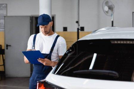 Photo pour Mécanicien dans le bouchon tenant presse-papiers et l'écriture près de la voiture - image libre de droit