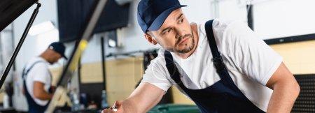 Photo for Panoramic shot of mechanic in cap repairing car near coworker in workshop - Royalty Free Image