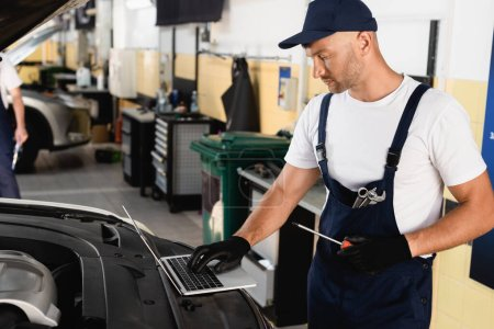 Photo for Auto mechanic typing on laptop on hood and holding screwdriver at service station - Royalty Free Image