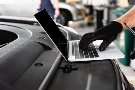Photo pour Vue recadrée du mécanicien automatique tapant sur ordinateur portable avec écran blanc sur la voiture à la station-service - image libre de droit