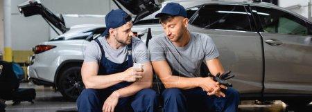 Imagen panorámica del mecánico de automóviles cansado sentado cerca de su compañero de trabajo y sosteniendo la taza de papel en la estación de servicio