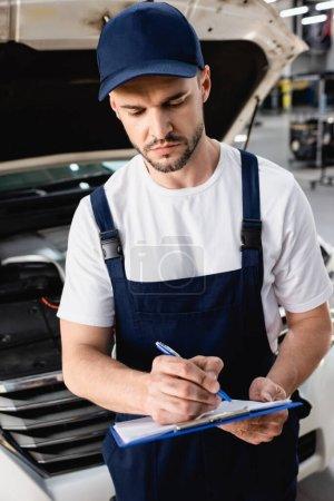 Photo pour Auto mécanicien écriture sur presse-papiers près du capot ouvert de la voiture à la station-service - image libre de droit