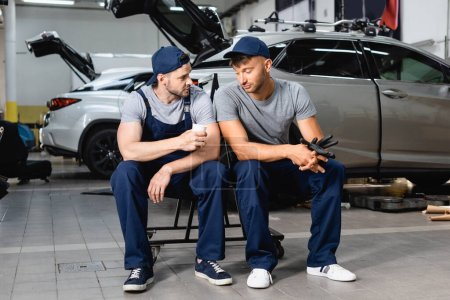 Tired auto mechanic sitting near coworker and holding paper cup at service station