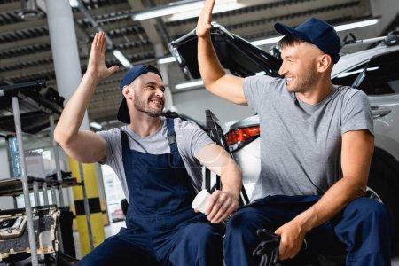 Photo pour Joyeux mécanicien automobile assis et donnant cinq élevé à un collègue à la station-service - image libre de droit