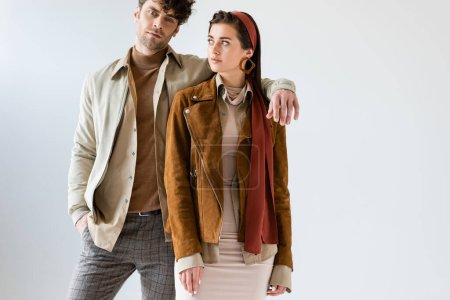 handsome man holding hand on shoulder of fashionable woman isolated on grey