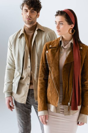 Photo for Fashionable man looking at camera near attractive girl in stylish suede jacket isolated on grey - Royalty Free Image