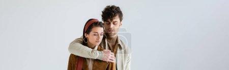 Photo for Horizontal image of handsome man embracing stylish woman isolated on grey - Royalty Free Image