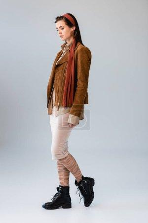 Photo pour Vue pleine longueur de jolie fille en tenue d'automne à la mode posant sur gris - image libre de droit
