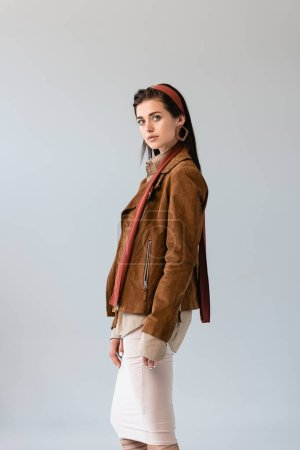 Photo for Attractive, fashionable girl in suede jacket looking at camera isolated on grey - Royalty Free Image